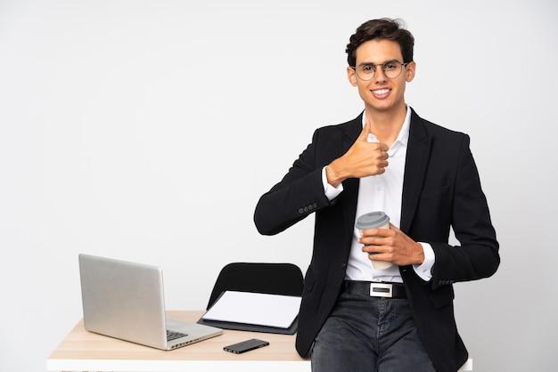 L'uomo d'affari nel suo ufficio sopra la parete bianca isolata che dà pollici aumenta il gesto
