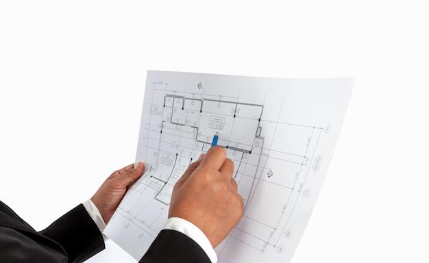 L'uomo d'affari nella mano ha un piano di costruzione o piano architettonico, utilizzato per il commercio di casa professionale correlato, immobiliare, costruzione.