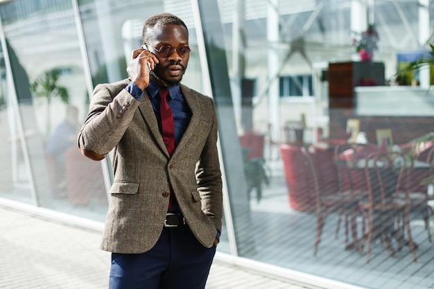 L'uomo d'affari nero afroamericano alla moda comunica sulla sua condizione dello smartphone