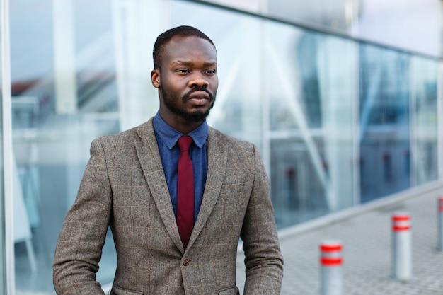 L'uomo d'affari nero afroamericano alla moda posa in un vestito prima di una costruzione moderna