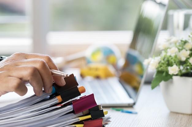 L'uomo d'affari passa la penna di tenuta per il lavoro in pile di archivi di carta che cercano le informazioni r