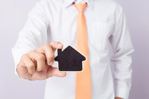 L'uomo d'affari passa la tenuta della forma di legno della casa del taglio, fondo isolato