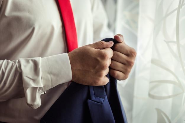 L'uomo d'affari porta un rivestimento politico, stile dell'uomo, primo piano delle mani del maschio, concetto dell'uomo d'affari, di affari, di modo e dell'abbigliamento