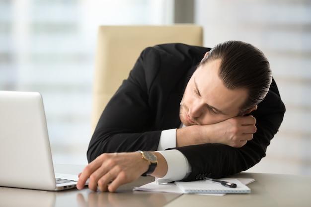 L'uomo d'affari prende la rottura e facente un pisolino in ufficio