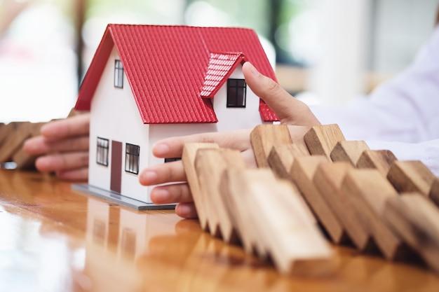 L'uomo d'affari protegge la caduta del blocco di legno alla pianificazione e alla strategia