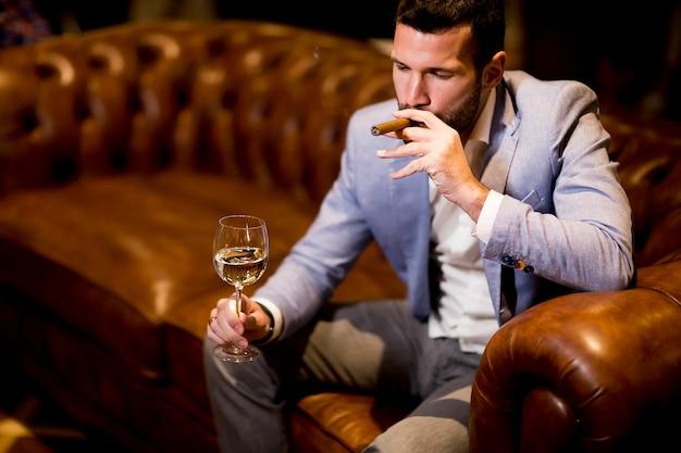 L'uomo d'affari ricco beve vino e fuma il sigaro