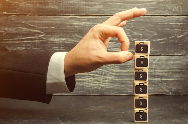 L'uomo d'affari rimuove un cubo con un'immagine dei dollari. crisi finanziaria ed economica.