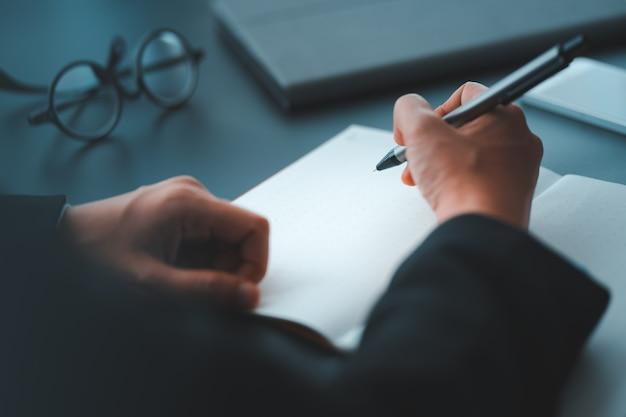 L'uomo d'affari scrive sul taccuino sullo scrittorio