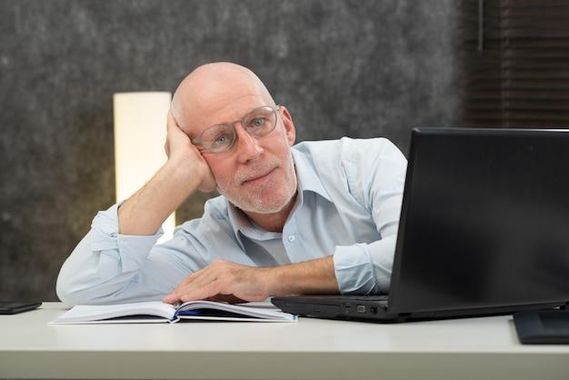 L'uomo d'affari senior è stanco nell'ufficio