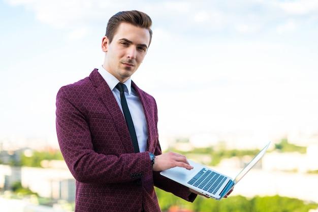 L'uomo d'affari serio in vestito e camicia rossi con il legame sta sul tetto con il computer portatile