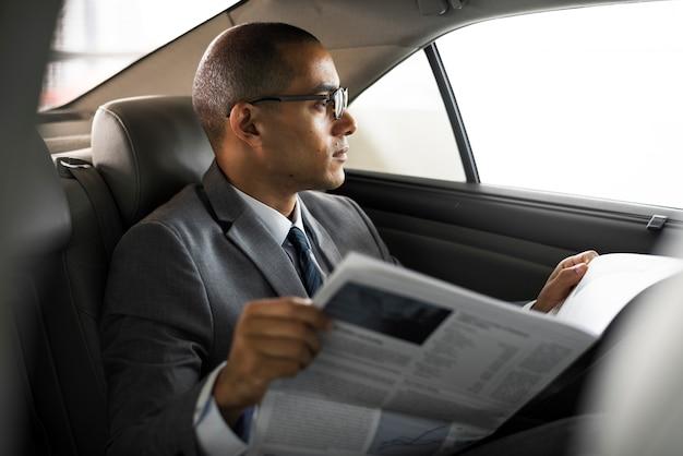 L'uomo d'affari si siede leggendo il giornale dentro l'automobile