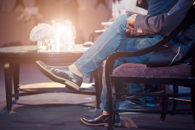 L'uomo d'affari si siede sulla poltrona e dà un discorso pubblico in una sala conferenze