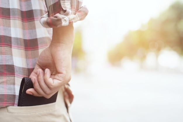 L'uomo d'affari sicuro che posa in sicuro mantenendo il vostro portafoglio nella tasca posteriore della sua tasca posteriore ansima.