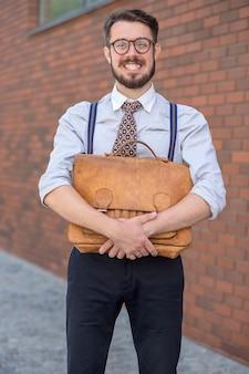 L'uomo d'affari sorridente con la vecchia valigetta in pelle retrò contro il muro di mattoni rossi