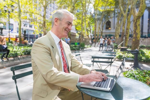 L'uomo d'affari sorridente lavora al computer al parco
