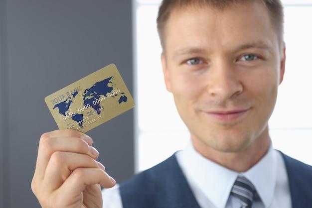 L'uomo d'affari sorridente tiene la carta di credito di plastica nella sua mano