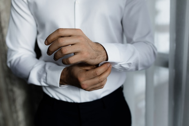 L'uomo d'affari sta indossando la camicia bianca, l'abbigliamento formale, si sta preparando per un incontro