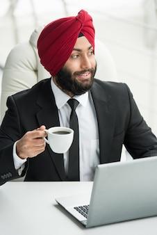 L'uomo d'affari sta lavorando al suo computer nell'ufficio.