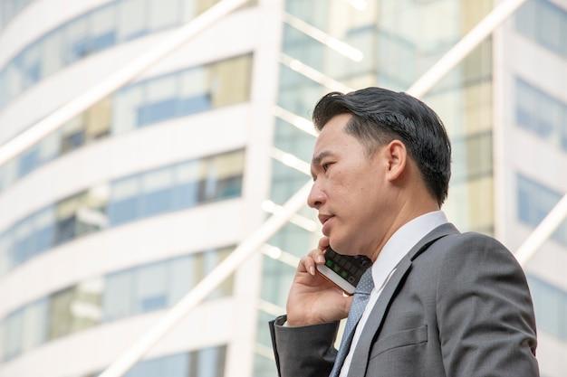 L'uomo d'affari sta parlando al telefono
