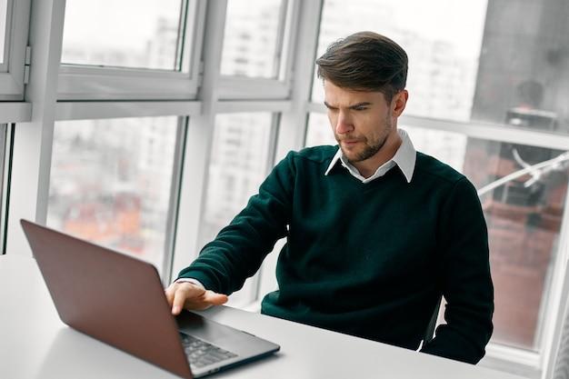 L'uomo d'affari sta scrivendo sul computer portatile nella stanza dell'ufficio