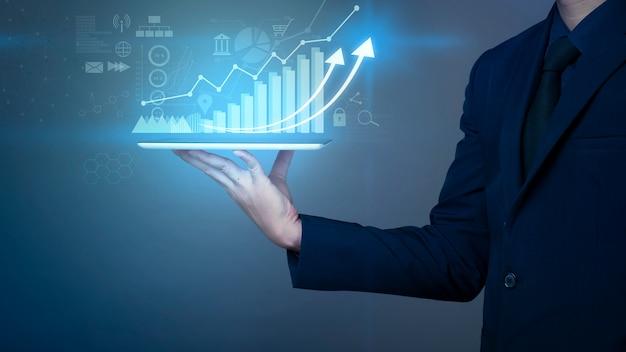 L'uomo d'affari sta tenendo il grafico della crescita finanziaria e sta analizzando i dati aziendali, il business plan e il concetto di strategia.