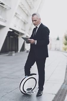 L'uomo d'affari sta usando un tablet pc su monowheel