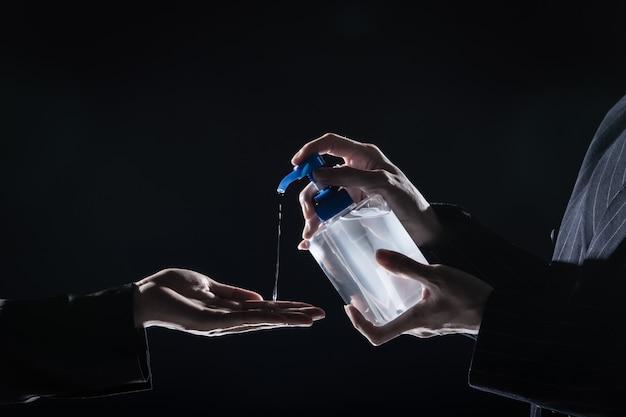 L'uomo d'affari stringe la mano a suit donna e pompa disinfettante alcool 70% gel per lavare l'igiene coronavirus o covid-19 prima di agitare, nuovo normale concetto di business lifestyle, bassa esposizione scura