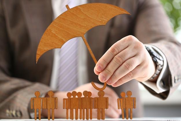 L'uomo d'affari tiene l'ombrello di legno a disposizione
