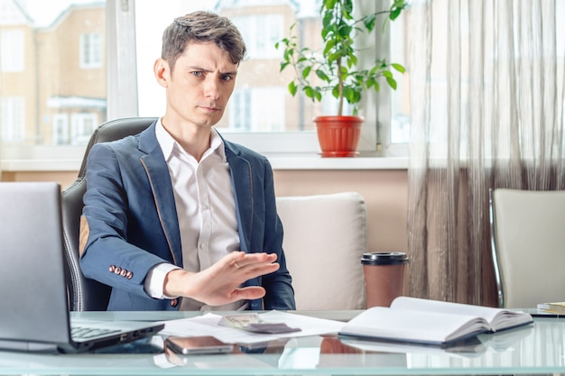 L'uomo d'affari ufficiale che si siede nel luogo di lavoro in ufficio rifiuta i doni.
