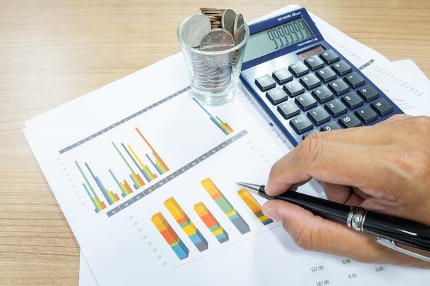 L'uomo d'affari usa una calcolatrice per calcolare per investimento, azione, miglioramento di affari, scambio, crescita di soldi.