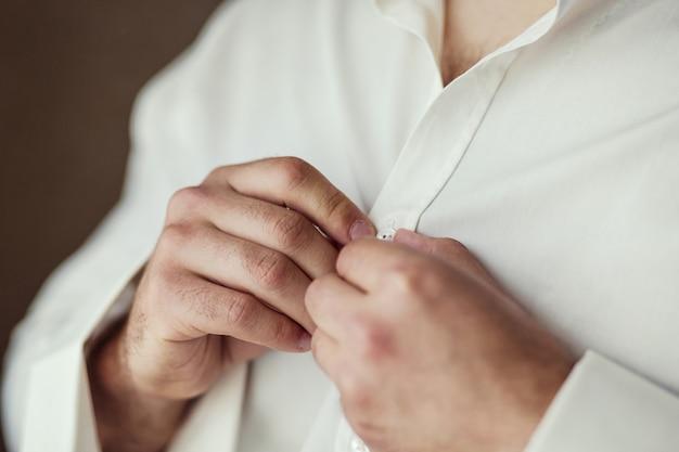 L'uomo d'affari veste la camicia bianca, il primo piano delle mani maschile, lo sposo si prepara al mattino prima della cerimonia nuziale,
