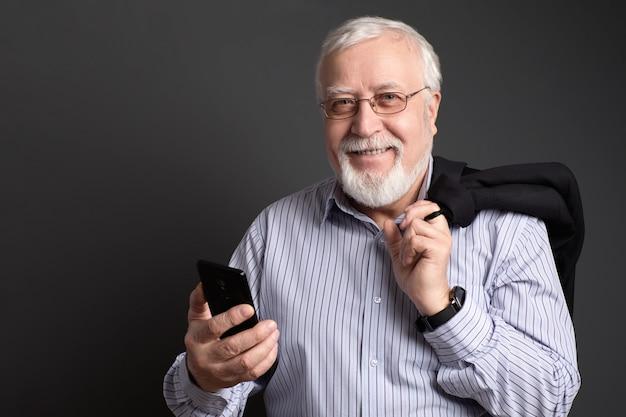 L'uomo dai capelli fini e dai capelli bianchi in vetri con un telefono su un fondo grigio sorride amichevole