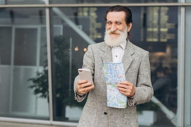 L'uomo dalla barba grigia senior che guarda lo smartphone e sorridere sta camminando lungo la costruzione dell'aeroporto