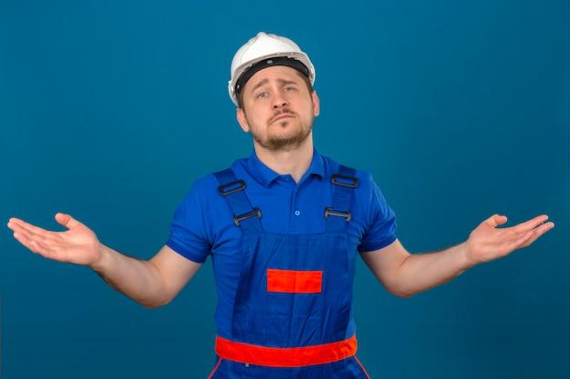 L'uomo del costruttore che indossa l'uniforme della costruzione e il casco di sicurezza ha un'espressione incerta e confusa con il concetto di dubbio sollevato mani e delle armi sopra la parete blu isolata