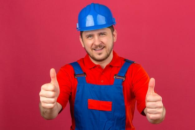 L'uomo del costruttore che indossa l'uniforme della costruzione e il casco di sicurezza sorridono mostrando amichevolmente i pollici su che controlla la parete rosa isolata