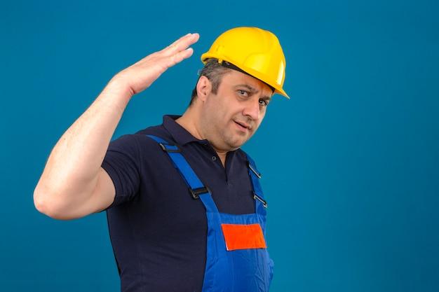 L'uomo del costruttore che indossa l'uniforme della costruzione e l'espressione confusa del casco di sicurezza con il braccio e la mano si sono alzati sopra la parete blu isolata
