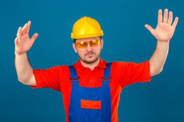 L'uomo del costruttore che indossa l'uniforme di costruzione e la discussione sul casco di sicurezza hanno litigio sollevando le mani che sembrano confuse con la faccia infastidita infastidita sulla parete blu isolata