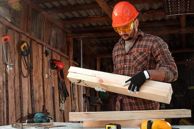 L'uomo del costruttore porta tavole sulla sua spalla