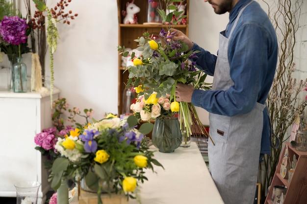 L'uomo del fiorista in grembiule fa un mazzo nel negozio di fiori per un regalo festivo per un matrimonio o un anniversario