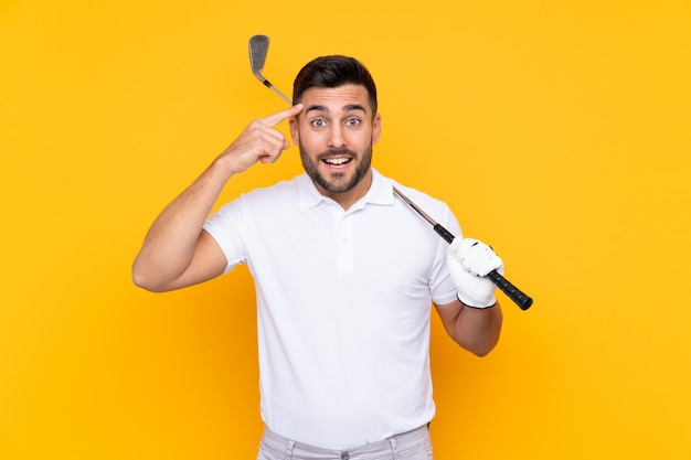 L'uomo del giocatore di golf sopra la parete gialla isolata che intende realizzare la soluzione