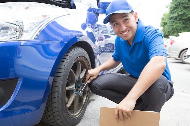 L'uomo del meccanico che tiene la lavagna per appunti e controlla l'automobile
