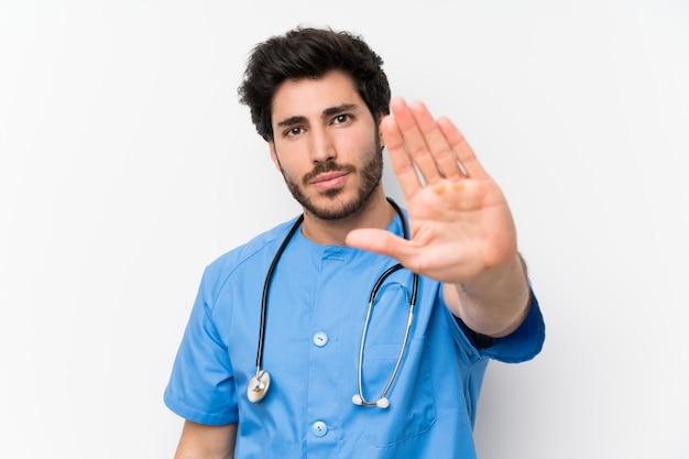 L'uomo del medico del chirurgo sopra la parete bianca isolata che fa il gesto di arresto con la sua mano
