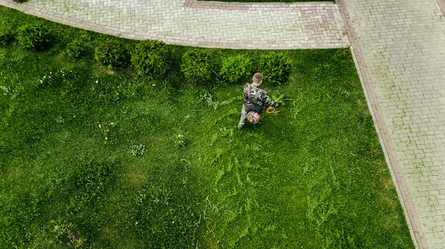 L'uomo del tosaerba falcia il prato dalla vista dall'alto