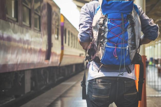 L'uomo del viaggiatore attende il treno sulla piattaforma ferroviaria