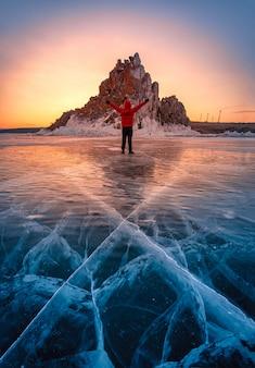 L'uomo del viaggiatore indossa i vestiti rossi e il braccio alzante che sta sul ghiaccio di rottura naturale in acqua congelata all'alba nel lago baikal, siberia, russia.