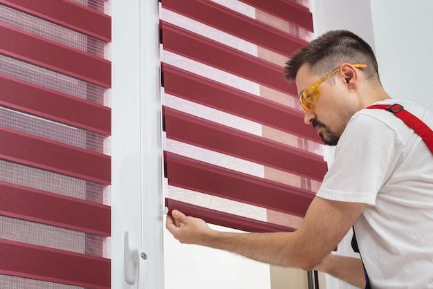 L'uomo dell'operaio di costruzione in un'uniforme installa le tende sulla finestra di plastica bianca in upvc