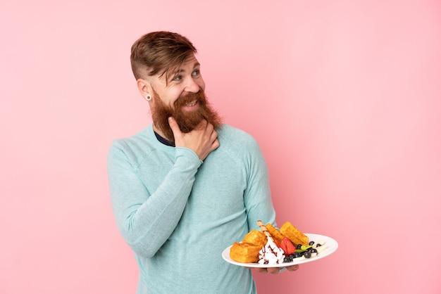 L'uomo della testarossa con la barba lunga che tiene le cialde sopra la parete rosa isolata che pensa un'idea e che guarda il lato