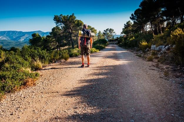 L'uomo della viandante cammina con uno zaino su una strada della montagna.