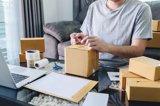 L'uomo delle pmi riceve il cliente dell'ordine e lavora con il mercato online di consegna della scatola di materiali di imballaggio sull'ordine di acquisto