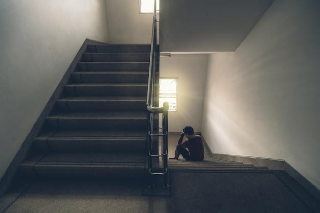 L'uomo depresso che si siede si dirige in mani sulla scala nell'uscita di sicurezza o sulla scala della costruzione